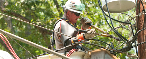 A crew man for Dominion Virginia Power works to restore electric power.