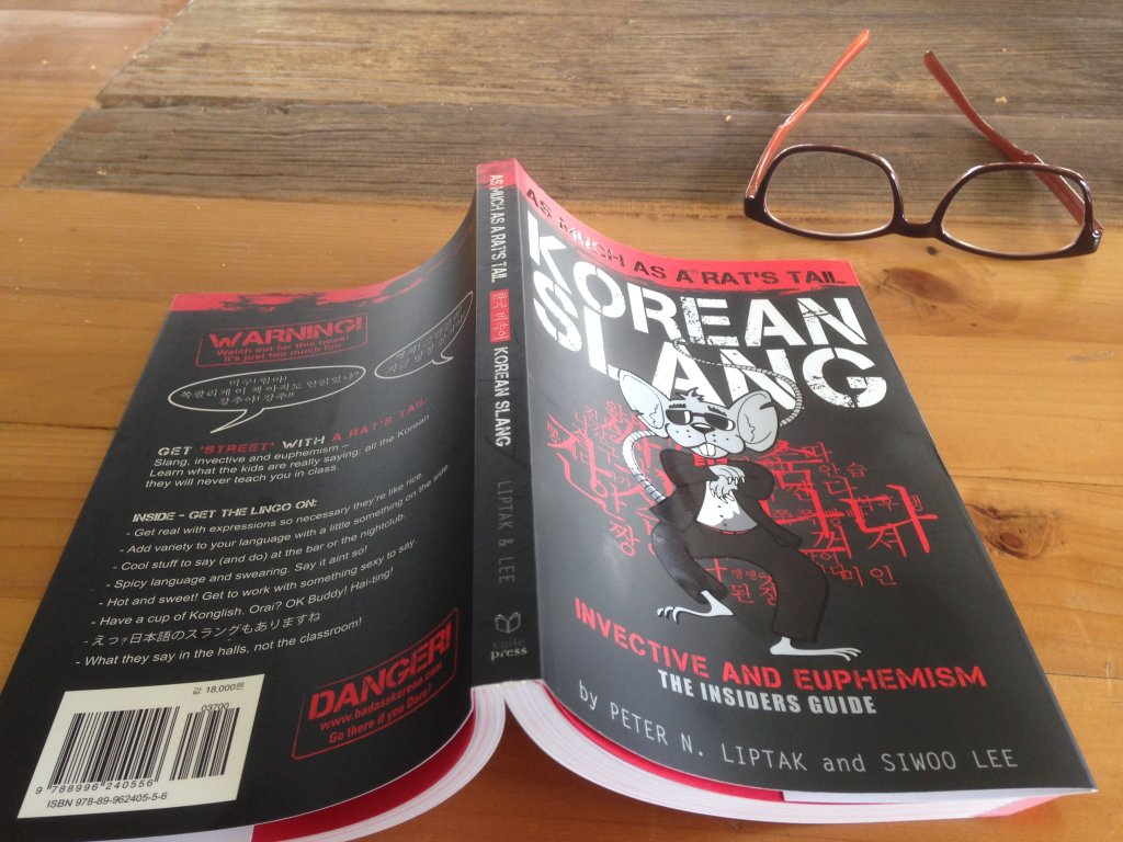 Korean Slang book open on table with glasses