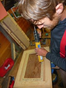 Josh using construction adhesive to attach the tempered glass to the door.
