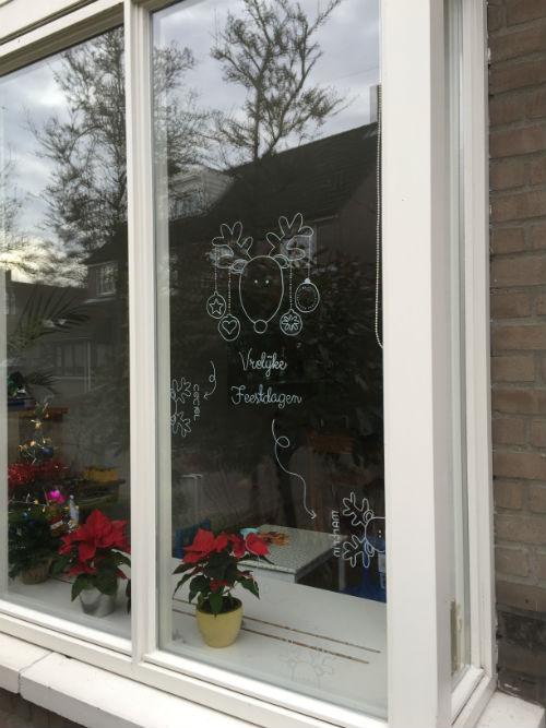 Raamtekening voor de feestdagen - kerstkaart op het raam