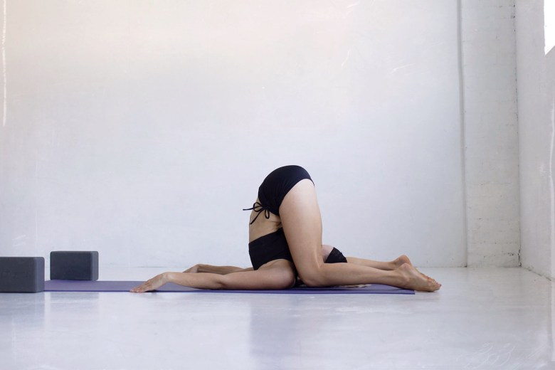 Ear pressure pose Karnapidasana manduka pro lite yoga mat and manduka yoga blocks and round bolster