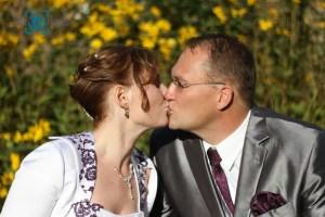 Hochzeit-Braut-Bräutigam-Hochzeitskleid-Anzug-Kuss-Paar-Glück-Sonne-Blumen-Baer.Photos-Fotograf-Holger-Bär