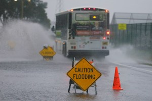 A bus passes through a flooded roadway Thursday, Dec. 11, 2014, in Mill Valley, Calif. A storm expected to be one of the windiest and rainiest in five years swept across the San Francisco Bay Area on Thursday, knocking out power to tens to thousands and delaying travel by air, train and ferry. Pacific Gas & Electric is reporting outages are widespread across the Bay Area due to weather, but officials weren't immediately available to give a specific number of outages.(AP Photo/Eric Risberg)