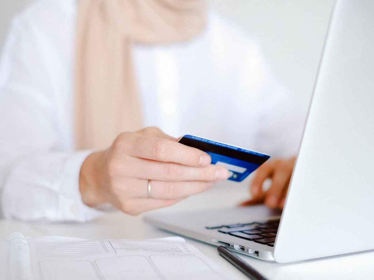 person in white long sleeve shirt holding credit card