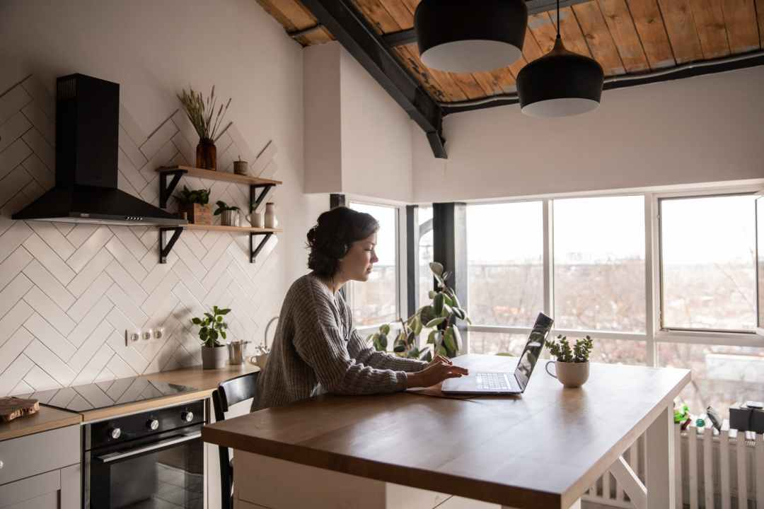 young woman surfing laptop in kitchen