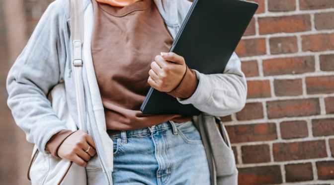woman with laptop near brick wall on street