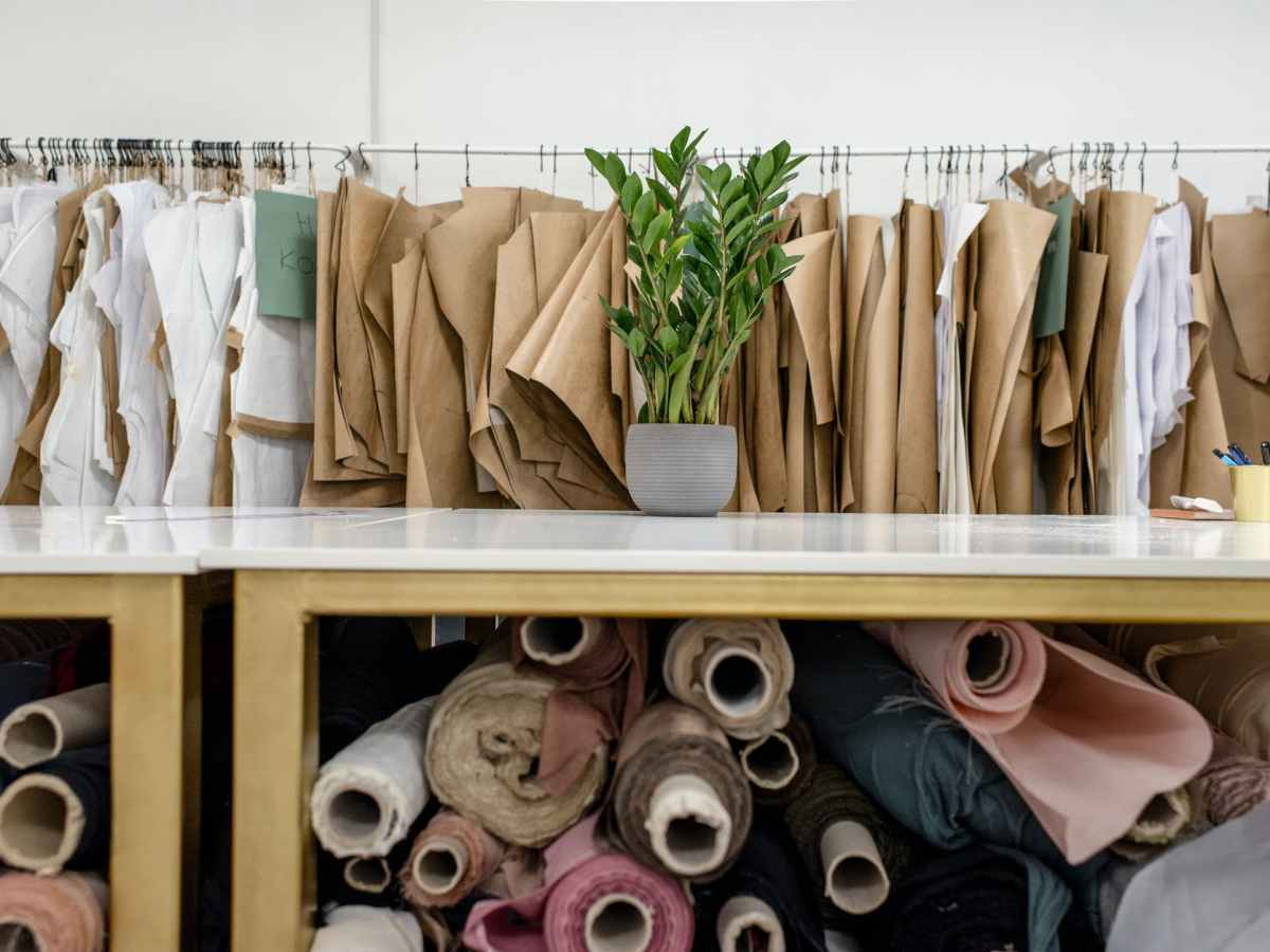 rolls of assorted fabrics and textiles and sewing patterns inside tailor atelier