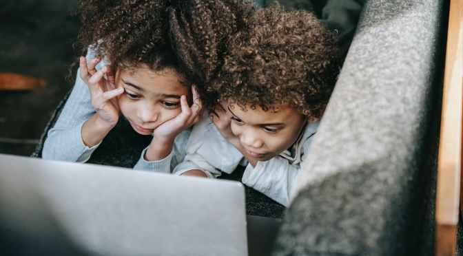 black siblings surfing internet on laptop on sofa at home