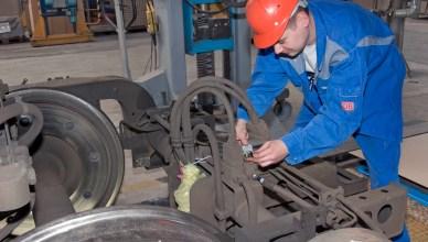Symbolbild: Mitarbeiter bei der Kontrolle von Kabelverbindungen an einem Drehgestell. (Foto: © DB AG / Jürgen Brefort)