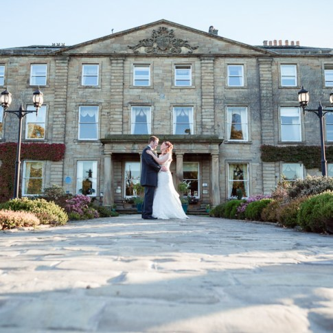 Watertown Park Yorkshire wedding venue with bride and groom holding hands in front of the stone building