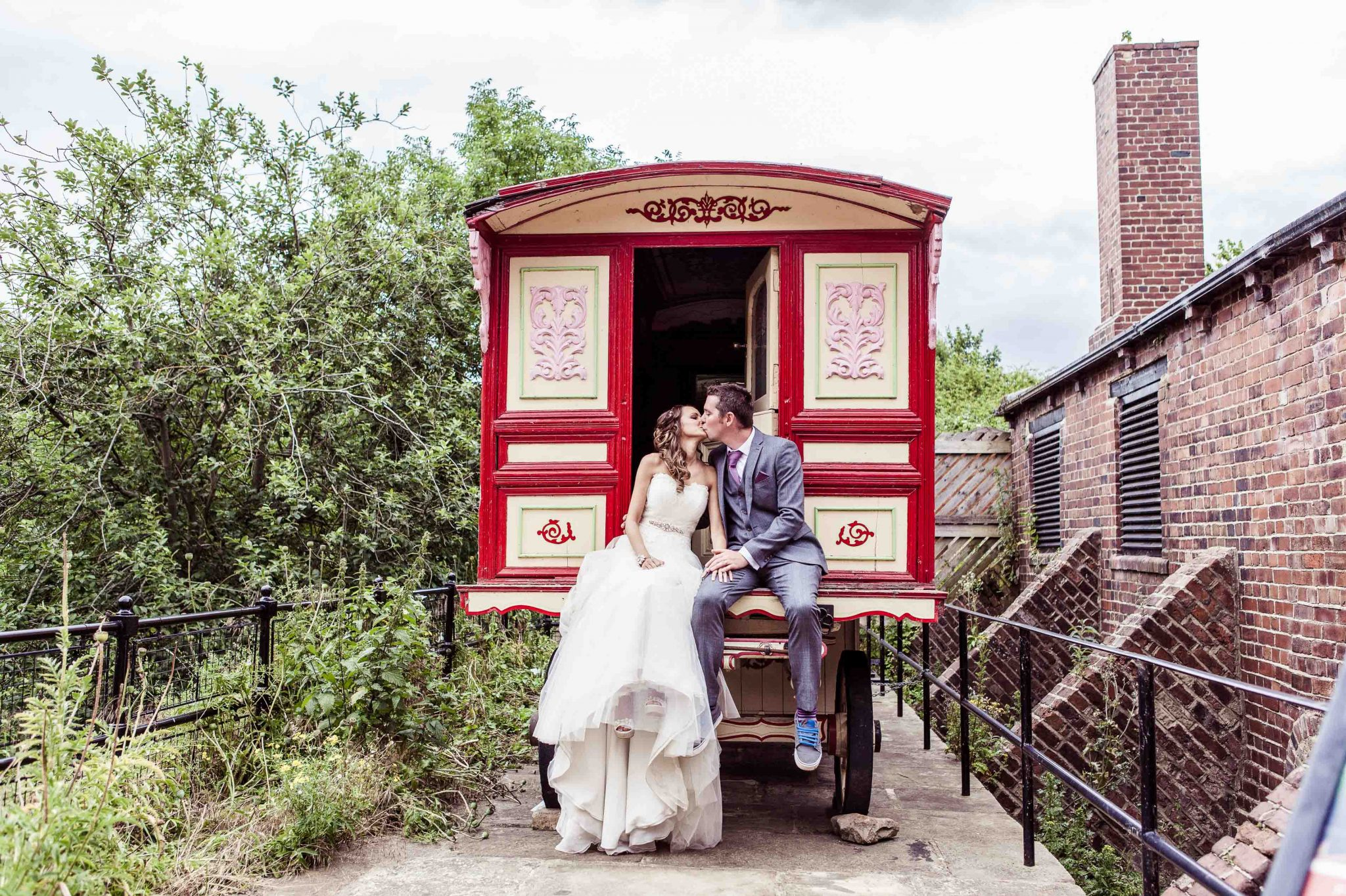Bride and Groom share a kiss, whilst seated on the gypsy caravan at the unique wedding venue Thwaites Mills in Stourton Leeds. Set amongst the red brick industrial backdrop of the Leeds wedding venue and waterwheel museum