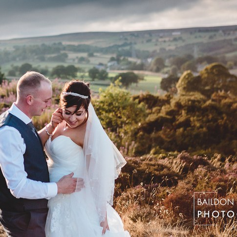 Bride and groom embrace, looking happy on Yorkshire moorland with views of Leeds villages. Photographed on a summer evening and backlit by the sun.