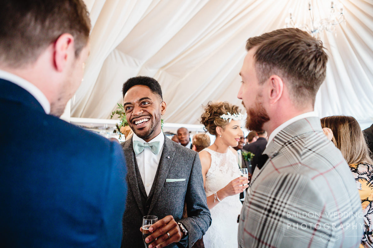 grinning groom talks to guests