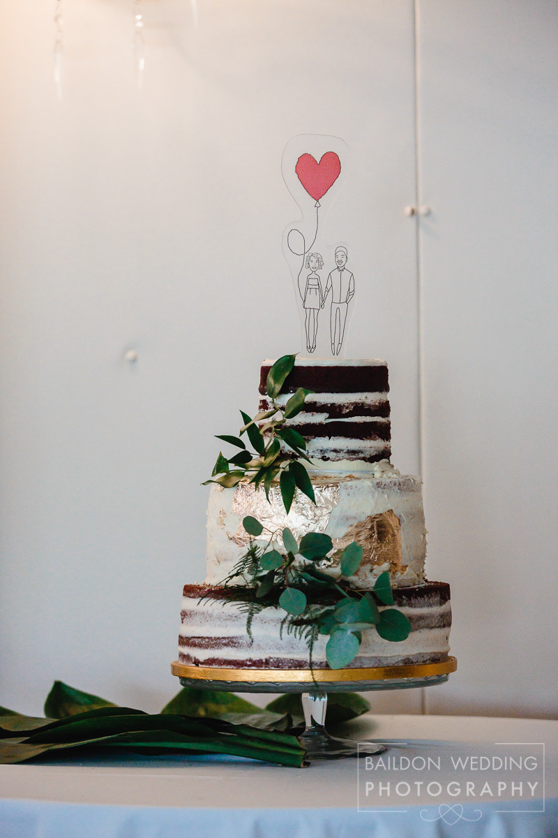 Modern take on a naked wedding cake with foliage