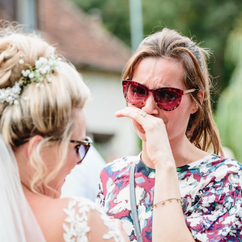 Emotional guest in tears talking to bride on her wedding day