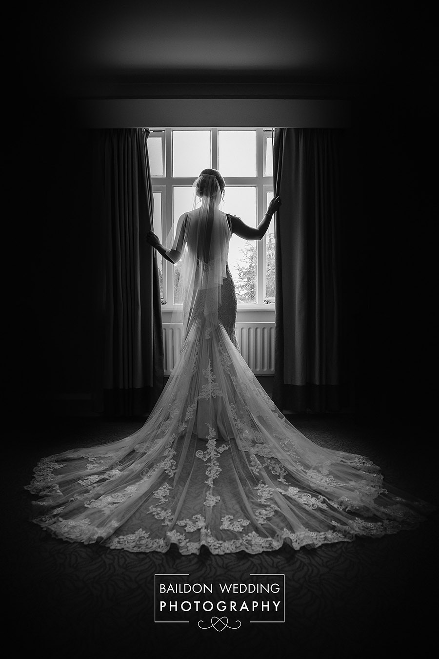 Bridal portrait in front of the window at Hollins Hall hotel near Leeds. Picture taken in the bridal suite