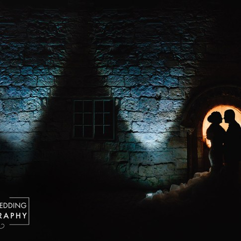 bride and groom are stood close to each other backlit silhouetted against stone cottage lit up at night Leeds wedding photographer