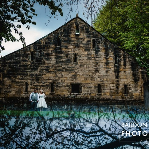 Bride and groom outside one of the barns at East Riddlesden Hall near the duck feeding lake on their wedding day