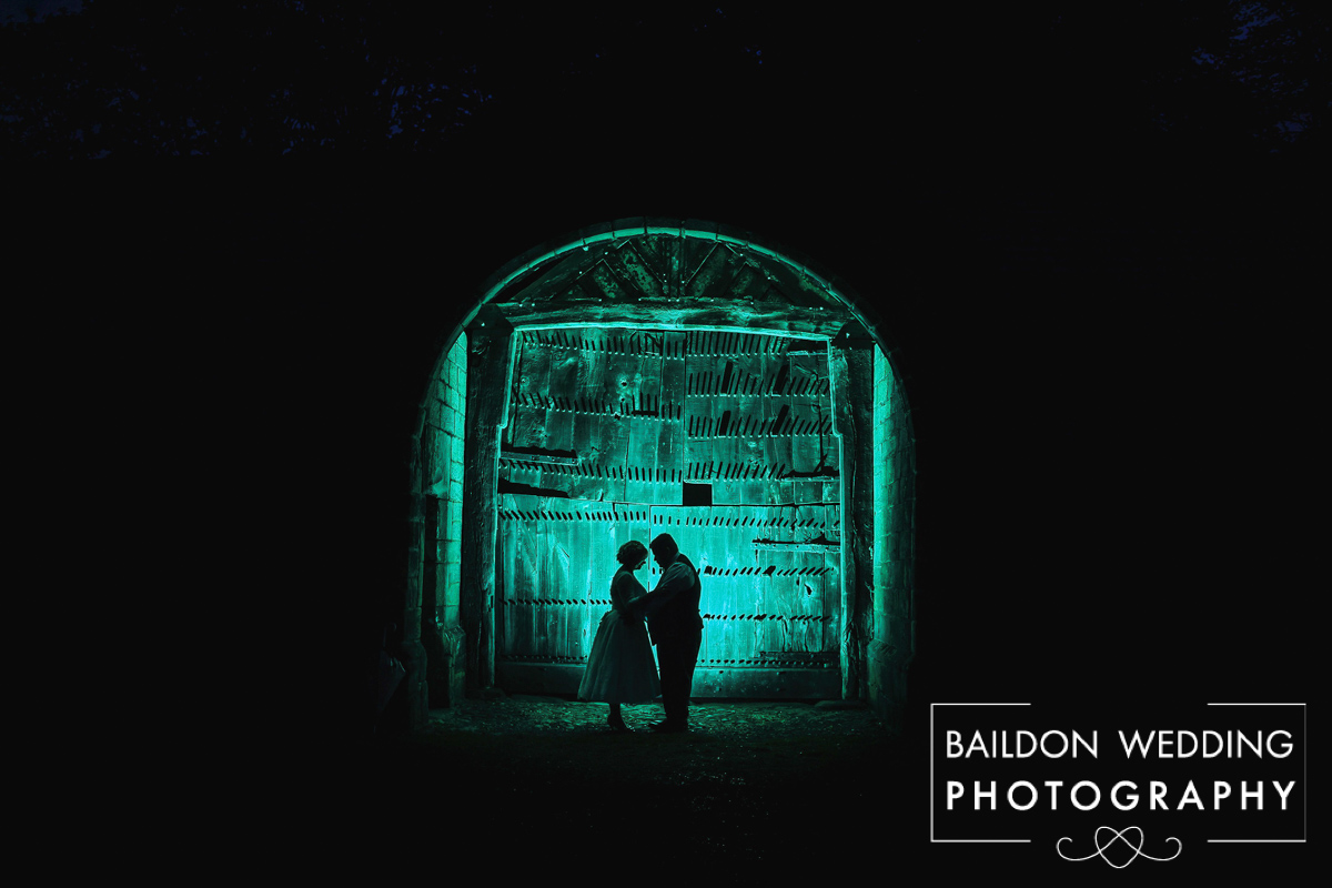 Gelled backlit photograph of bride an groom in barn door yorkshire