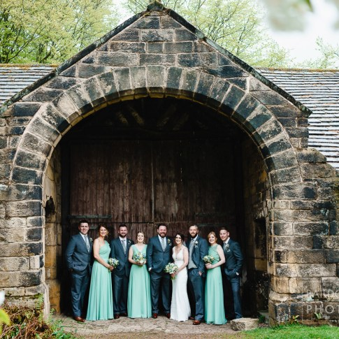 Group shot from spring wedding at East Riddlesden Hall in barn door way due to rain
