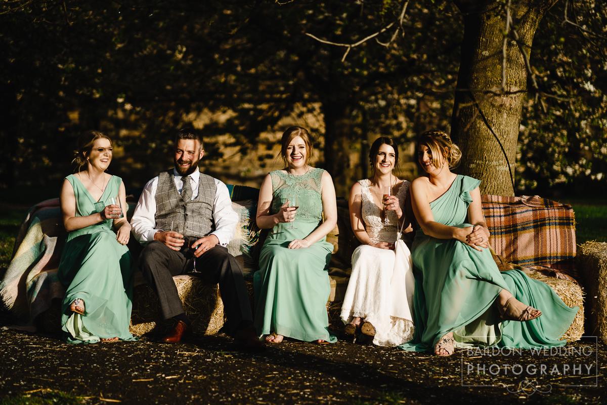 Bridesmaids on hay bales rustic wedding