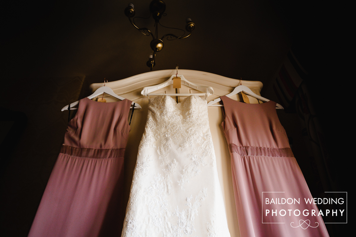 Bridesmaids dresses hung on wardrobe