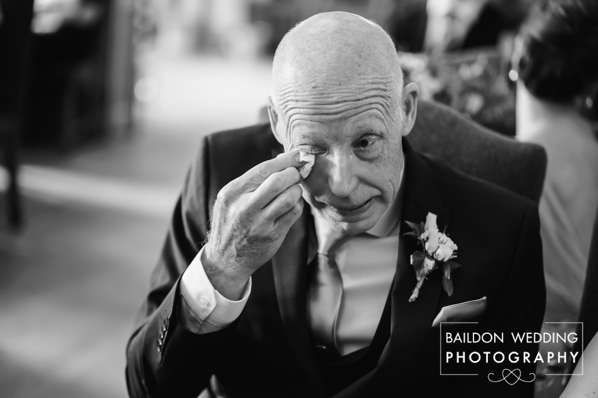 Father of the bride cries during the wedding ceremony as he watches his daughter getting married