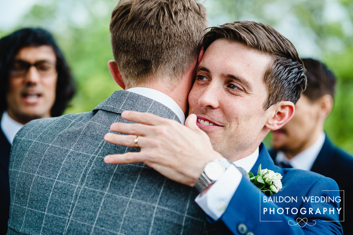 Groom hugs friends