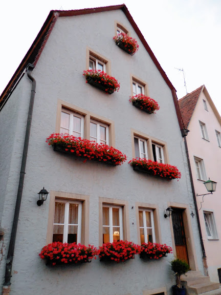 Hotel Gasthof blue house with red flowers in window boxes