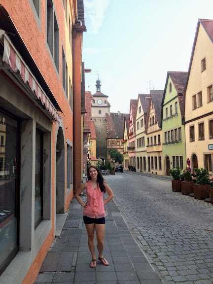 woman stands on street with half-timbered houses in Rothenburg ob der Tauber