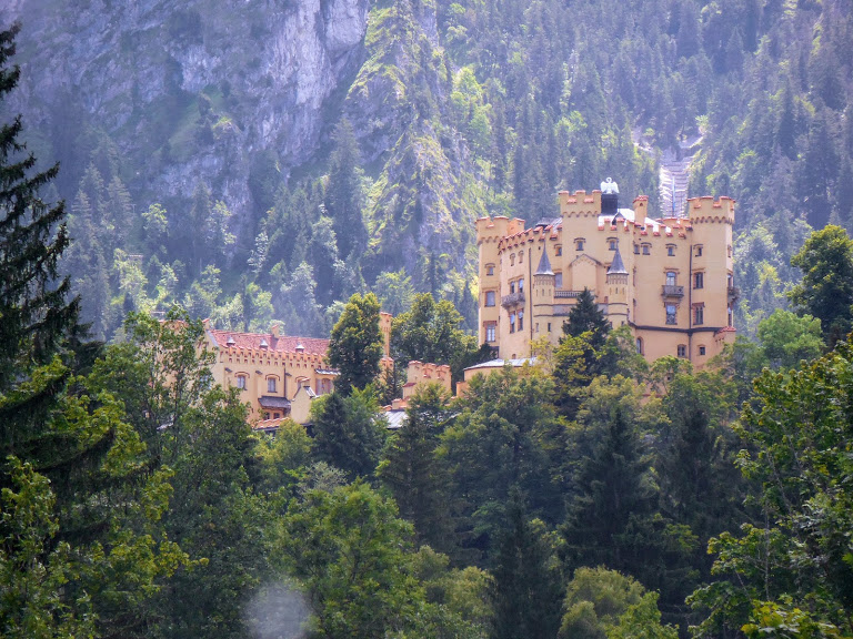 Schloss Hohenschwangau sits atop a hill with mountains behind