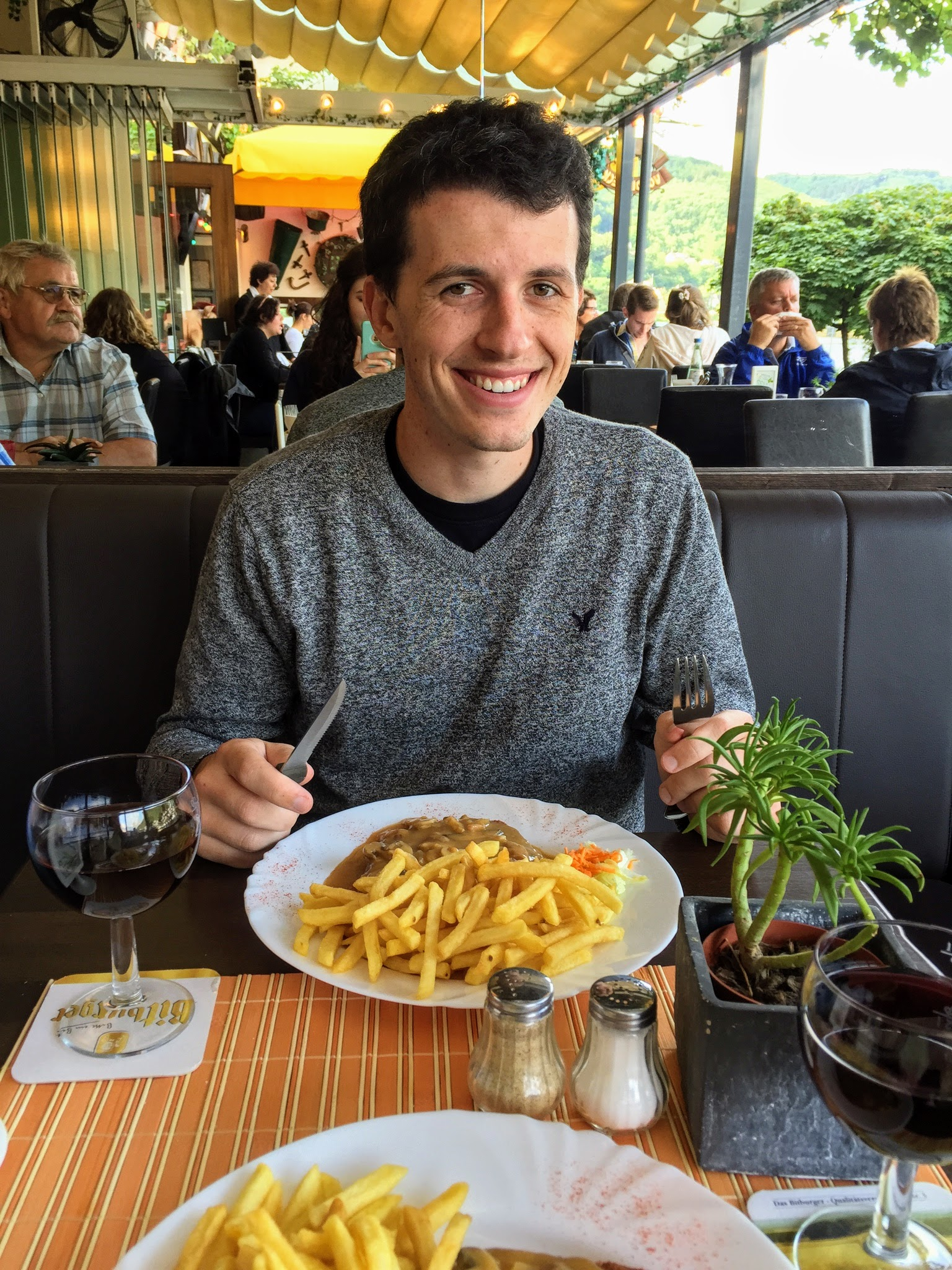 man sits at riverfront restaurant in Cochem eating snitzel with wine