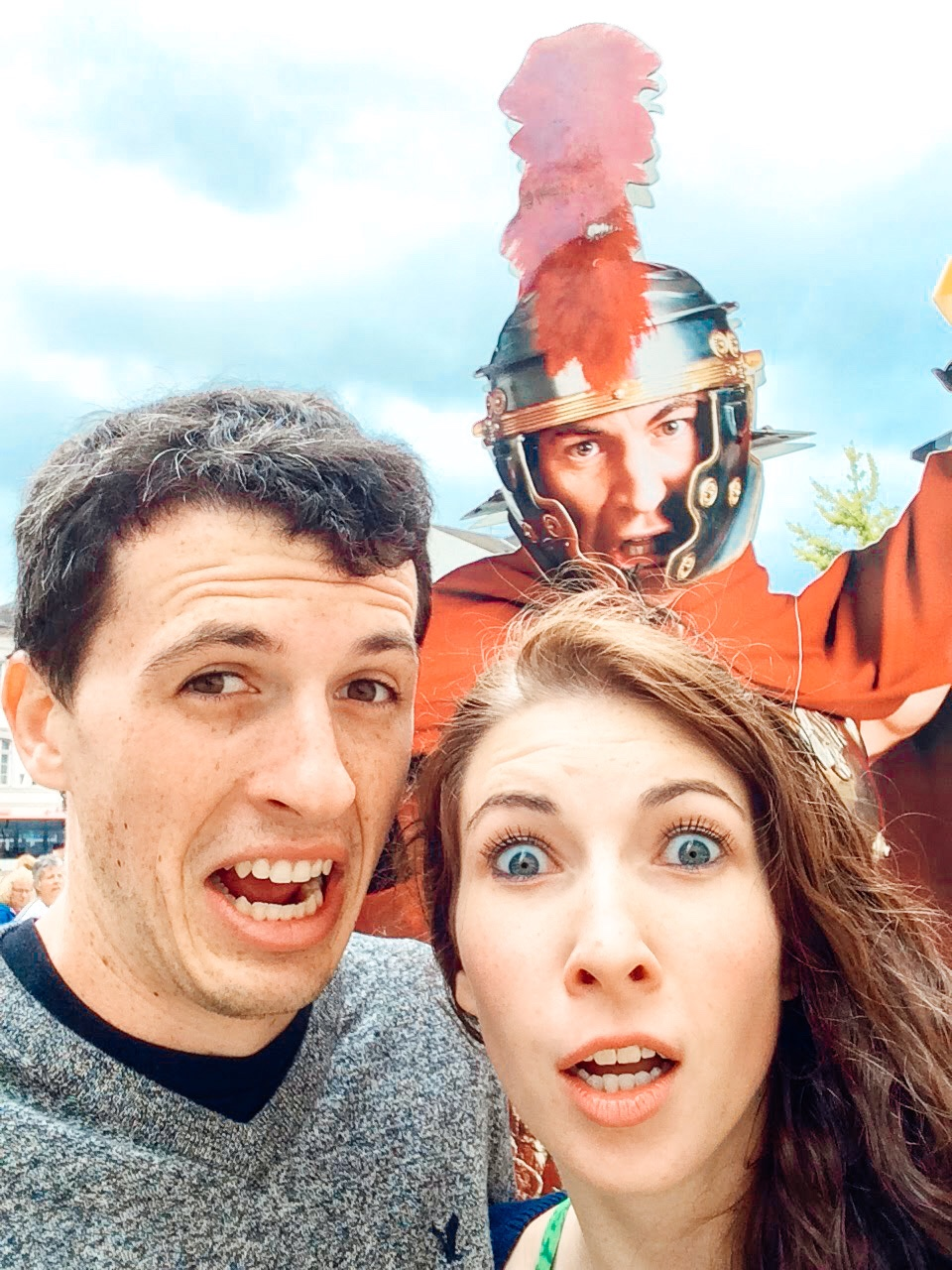 man and woman pose with cutout of ancient Roman soldier