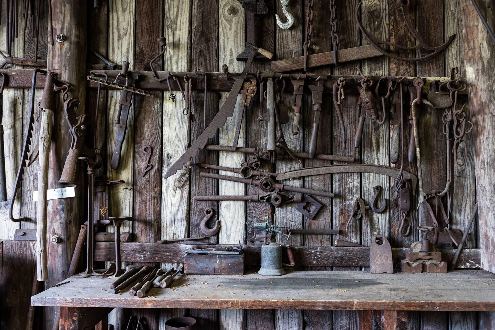 black metal tools hanged on a rack near table
