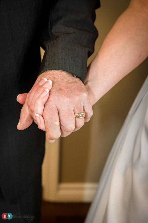 Bride and father of the bride hand in hand
