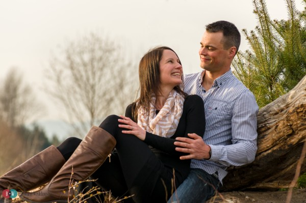Engaged couple smiling at each other on tree