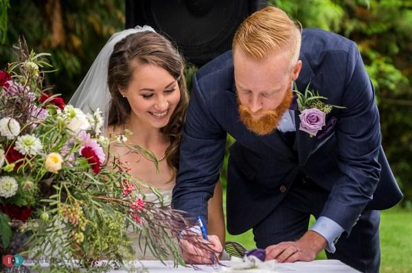 Groom beside bride signing wedding register