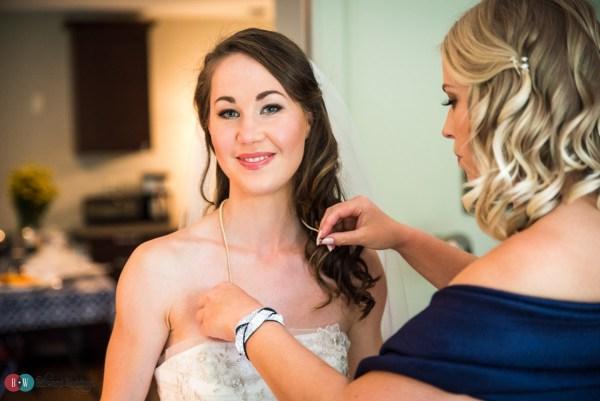 Bridesmaid Putting Brides Necklace on