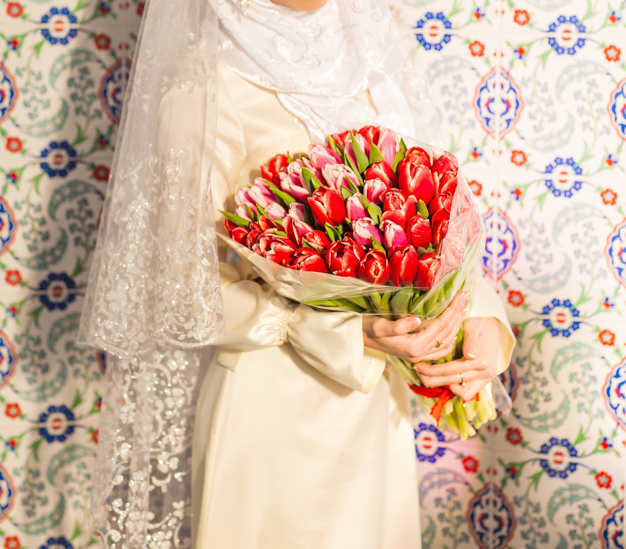 Young bride in islamic clothes posing with flowers indoors