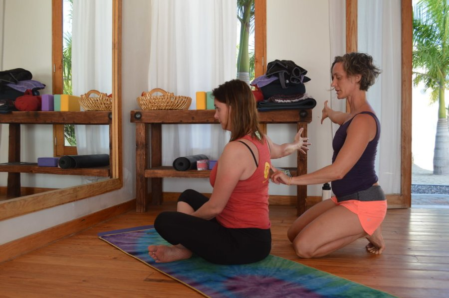 yoga teacher assisting student