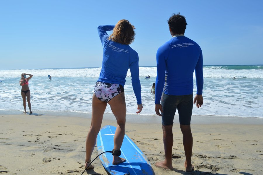 woman learning to surf looks out on the ocean with her surf instructor