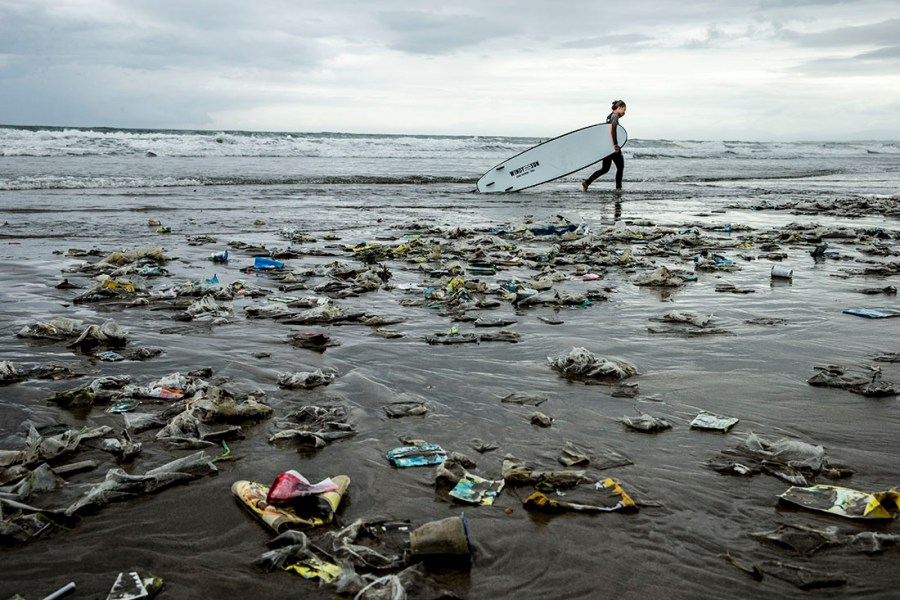 surfer walks a beach littered with plastic