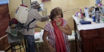 Una mujer se cubre la boca mientras un brigadista fumiga su casa