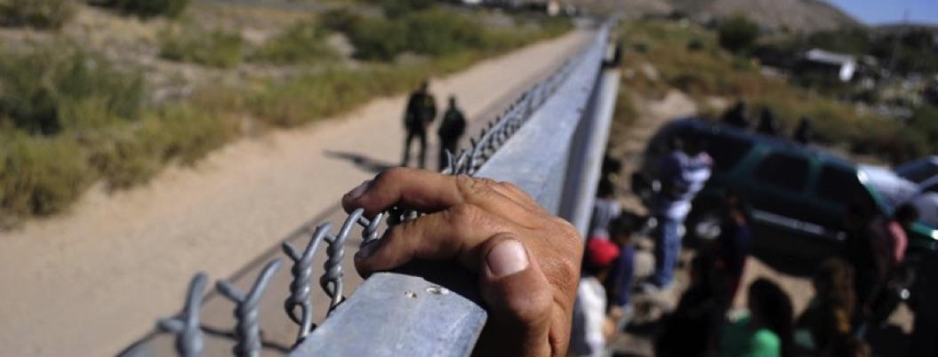 Migrantes trepan muro fronterizo; EU les arroja gas lacrimógeno