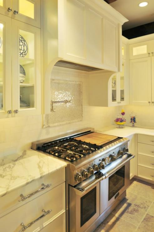 kitchens - calcutta gold countertops subway tiles backsplash marble mosaic tiles backsplash pot filler white glass-front shaker kitchen cabinets polished nickel hardware