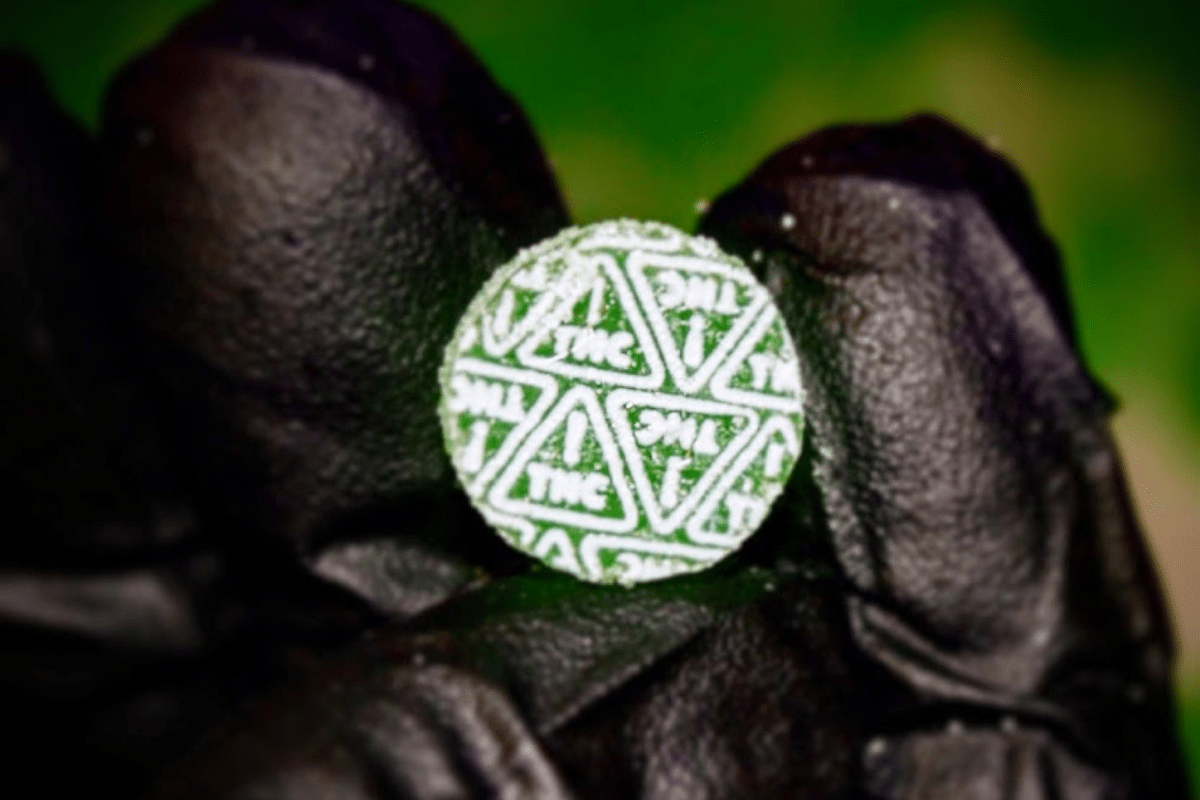 green gummy with white thc symbols on top