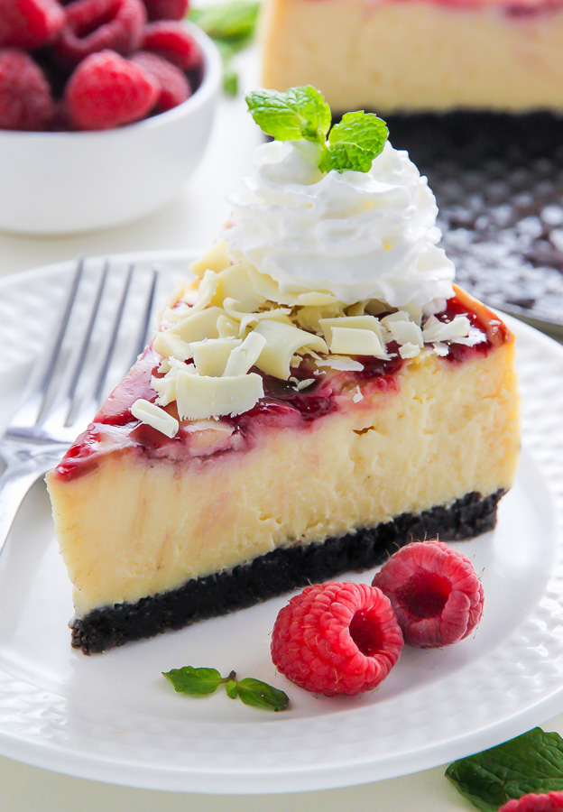 Creamy White Chocolate Cheesecake swirled with fresh raspberry, all on top of a homemade chocolate cookie crust. This one is a showstopper!