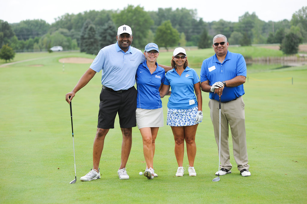 two men and two women on golf course