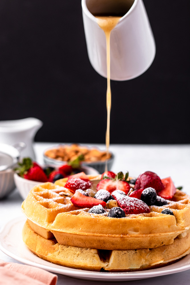 Buttermilk being poured on waffles with berries