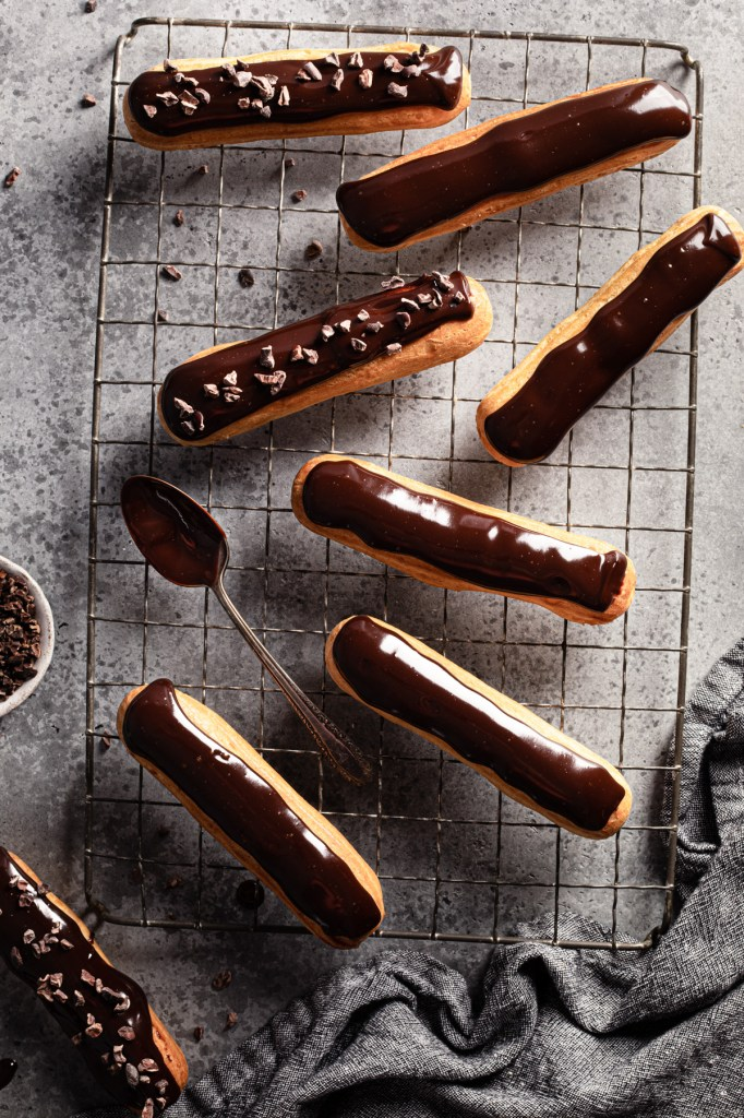 flatlay of eclairs filled with pastry cream and topped with chocolate ganache